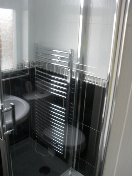 Photo - Contemporary Bathroom (2 of 3) - View through shower unit of chrome heated towel rail. - Fitted Kitchens and Bathrooms - Home - © J C Joinery