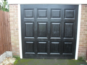 Photo - Georgian style matt black automatic up and over GRP garage door with wood grain effect
